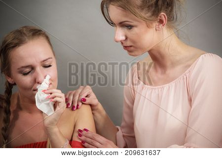 Female comforting her woman friend while she is sad and depressed blowing runny nose into paper tissue.