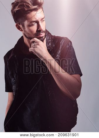 Portrait of young handsome fashionable man against wooden wall.