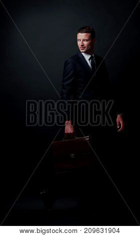 Portrait of a business man  with briefcase isolated on black background