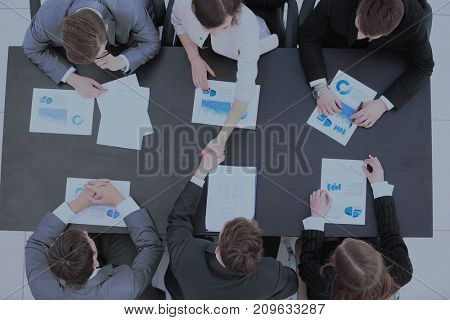 business partners shake hands after a discussion of a new financ
