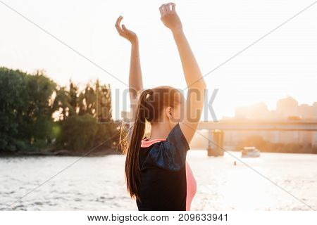 girl in sportswear doing exercises before jogging at sunset on the river bank