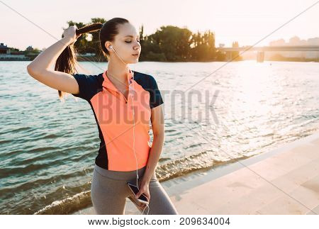 girl in sports clothes listening to music on a run at sunset on the river bank