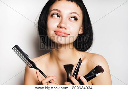 nice girl with black short hair mysteriously looks away and holds in her hands makeup brushes and a comb