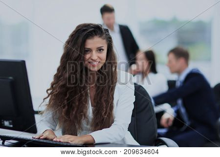 Happy young businesswoman looking behind and her colleagues work