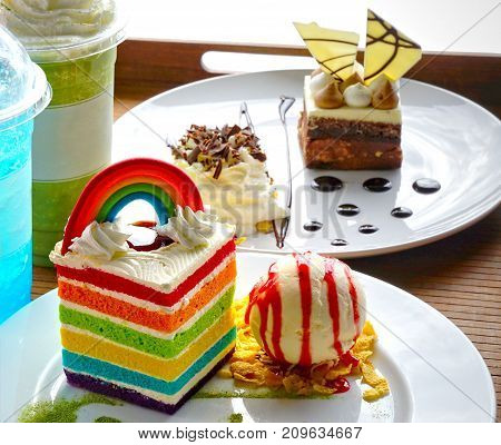 Piece of rectangular shape velvet rainbow cake with scoop of vanilla ice cream on white plate