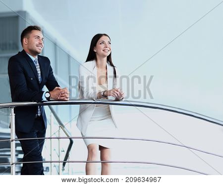 Portrait of positive business group standing on stairs of modern office