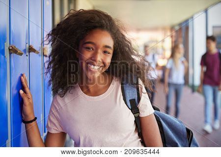 Portrait of black teenage girl by lockers in school corridor