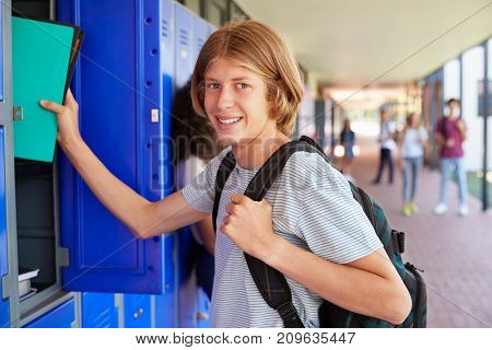 White teenage boy using locker in school corridor