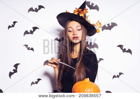 a young sexy gothic girl in the shape of a witch in halloween, in a big black hat, holding a pumpkin and a magic wand