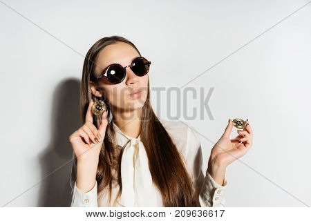 young successful modern business lady in sunglasses holds a golden bitcoin in hands