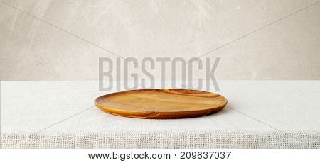 Empty round wooden tray on sack tablecloth background banner food display montage food background