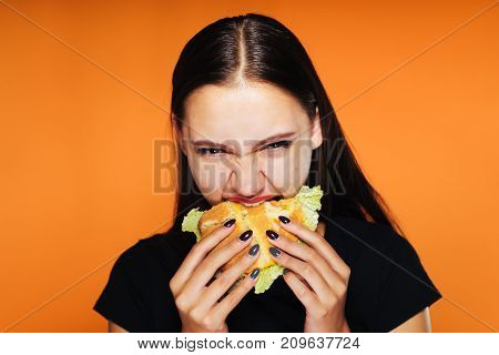 The girl greedily eats a burger and looks angrily at the camera. tasty food, isolated on orange background