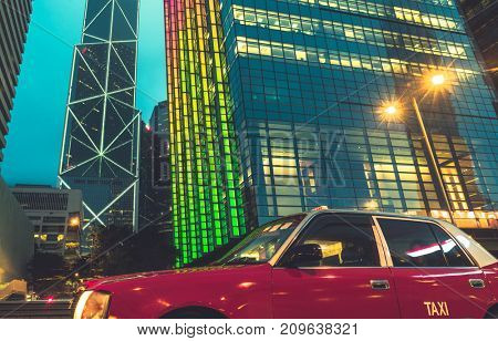 red taxi driving on road with illuminated modern skyscrapers on background, hong kong,china,asia.