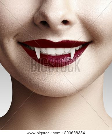 Sexy female vampire lips. Halloween background with red blood makeup lip and black copyspace. Masquerade look with terrible fags