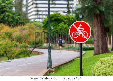 Man jocking on the way of city public park with the sign of bike not allowed