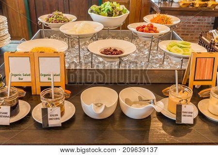 Various vegetable and dressing for salad on box of ice cube on wooden table in restaurant