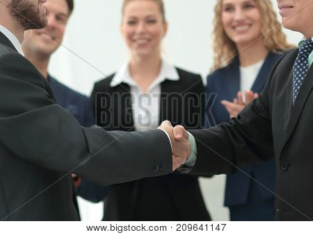 Mature businessman shaking hand of  his partner with colleagues