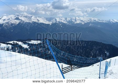 View of the mountains through the fence in a ski-resort in winter period