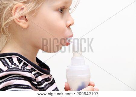 Child using inhaler isolated on white background. Theme of treatment of children's respiratory illness.