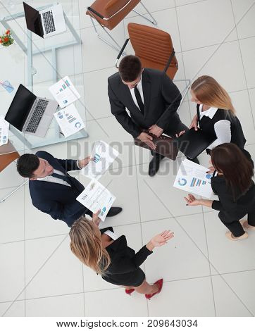 view from the top.business team discussing marketing charts,standing in the office.