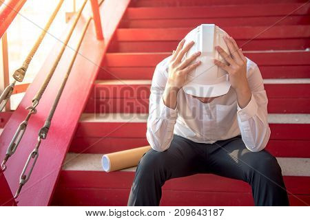 Engineer or Architect feeling tired and headache with his job. sitting on building stairs with architectural drawing on his side while wearing protective equipment safety helmet at construction site