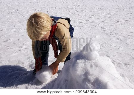 Boy 3 years old playing with snow in winter. Denim overalls, scarf. Blond hair.