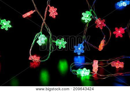 Multi-colored Lights In The Form Of Snowflakes On A Black Background