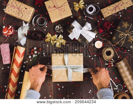 Man tying bow on christmas gift box. Process of package new year gift box. Christmas packaging wrapping paper ribbon twine bow and thread scissors christmas balls on wooden background. Winter time new year