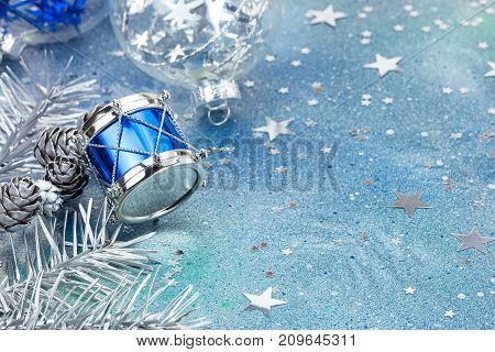 Blue Drum With Silver Fir Tree Branches On Blue Background With Star Confetti