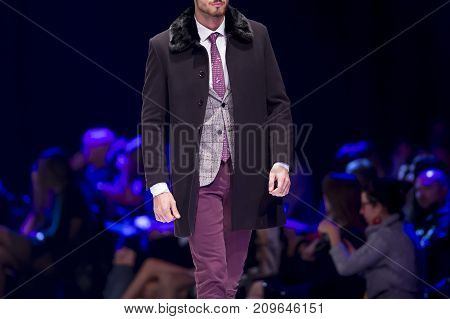 Sofia, Bulgaria - 28 September, 2017: Male model walks the runway in stylish suit during a Fashion Show. Fashion catwalk event showing new collection of clothes. Single model. Blue background.