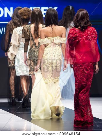 Sofia, Bulgaria - 28 September, 2017: Female models walk the runway in different dresses during a Fashion Show. Fashion catwalk event showing new collection of clothes. Seen from the back.