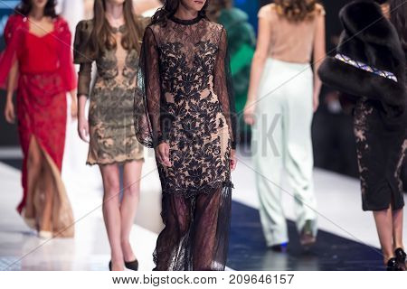 Sofia, Bulgaria - 28 September, 2017: Female models walk the runway in different dresses during a Fashion Show. Fashion catwalk event showing new collection of clothes. In a row.