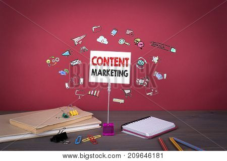 Content Marketing concept. Wooden table at the red background.