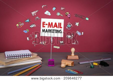 Email Marketing concept. Wooden table at the red background.