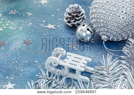 Silver Christmas Decorations With White Sledge On Blue Background Covered With Star Confetti