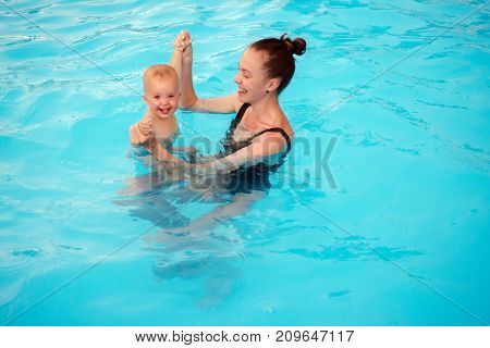 Mother teaches to swim an one-year-old kid into the pool. Mum with baby having fun