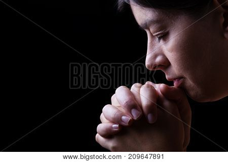 Faithful woman praying, hands folded in worship to god with head down and eyes closed in religious fervor, on a black background. Concept for religion, faith, prayer and spirituality.