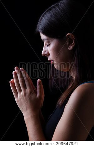 Faithful woman praying, with hands folded in worship to god, head down and eyes closed in religious fervor, on black background. Concept for religion, faith, prayer and spirituality