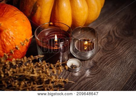 composition for decorating the house for halloween, lie yellow and orange pumpkins on each other, burning scented candles, lies a branch of dry grass