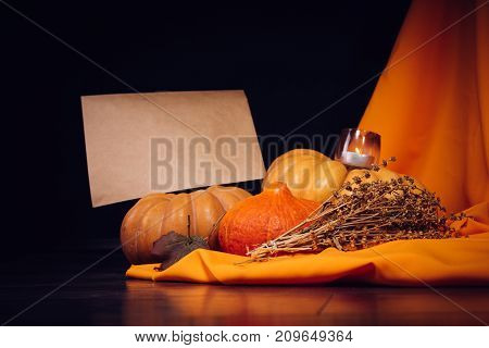 composition for decorating the house for halloween, lie yellow and orange gourds, burning scented candles on the background of orange curtains