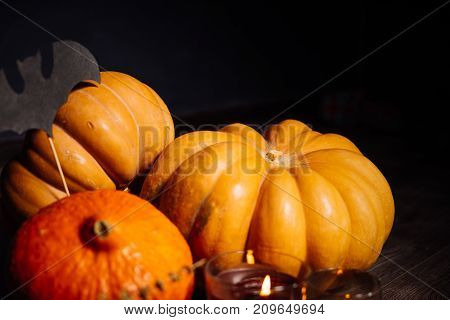 composition for decorating the house for halloween, lie yellow and orange pumpkins, burning scented candles
