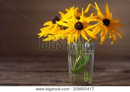 Yellow flowers of a gerbera in a glass. A bouquet from three flowers in a glass transparent thick glass tumbler on a wooden table. Close up selective focus free space left