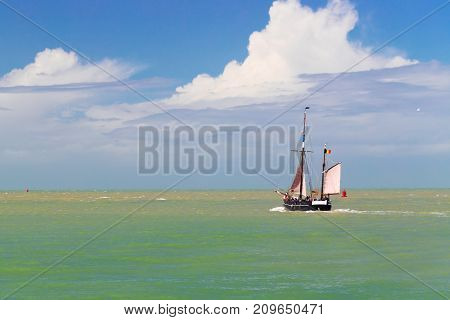 The sailing vessel goes to the high sea. At the sea a storm water muddy in the sky the leaving cloud but shines the sun. On the sailing vessel a flag of Belgium