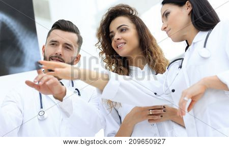 group of medical workers looking at patient's x-ray film