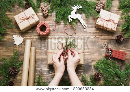 Christmas giftbox and present boxes wrapping in craft paper and decor on wooden board. Top view of hands on wooden table with fir tree branches, decoration of gift. Flat lay. Top view. Creative hobby.