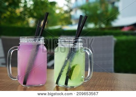 Glass mason jars with fresh drinks on table outdoors