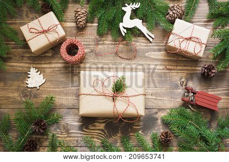 Christmas giftbox and presents wrapping in craft paper and decor on wooden board. Flat lay. Top view. Creative hobby.