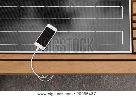 Mobile phone charging on bench with solar panel