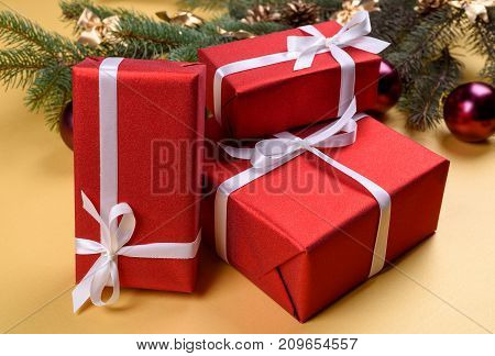 Christmas background with red gift boxes fir tree branches with glass balls and pine cones on golden background free space. Red luxury New Year gift copy space