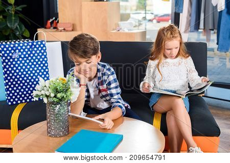brother and sister reading magazines while sitting on sofa in boutique during shopping